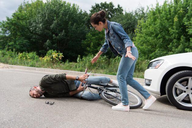 водитель подходит к упавшему велосипедисту