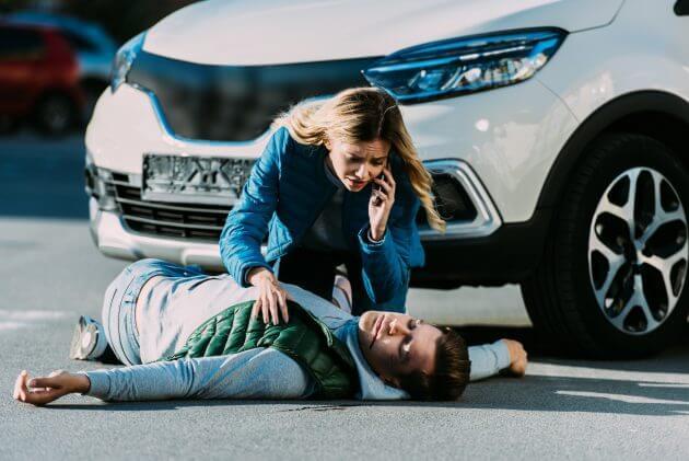 Сбитый автомобилем парень лежит на дороге