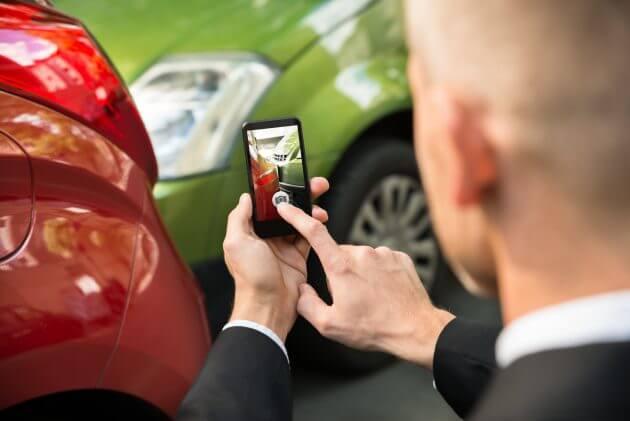 Парень фотографирует аварию на телефон