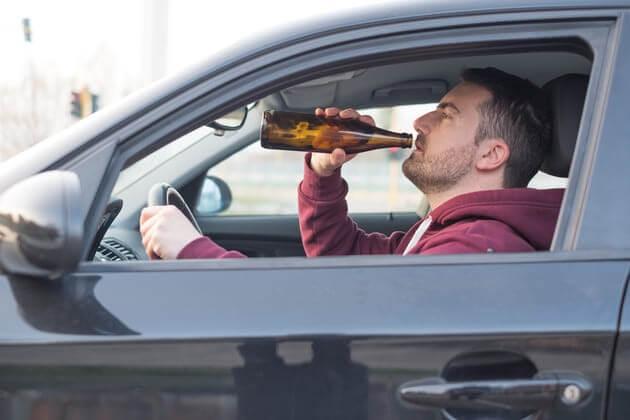 Водитель авто пьет пиво за рулём