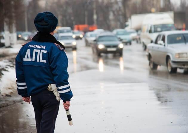Инспектор ГИБДД стоит на дороге