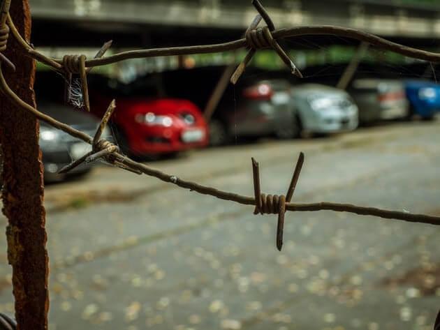 Территория с автомобилями обнесена колючей проволокой