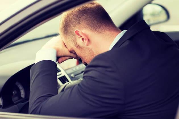 Расстроенный водитель положил голову на руль автомобиля