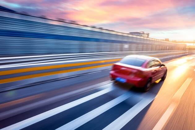 Автомобиль, едущий на автостраде на закате