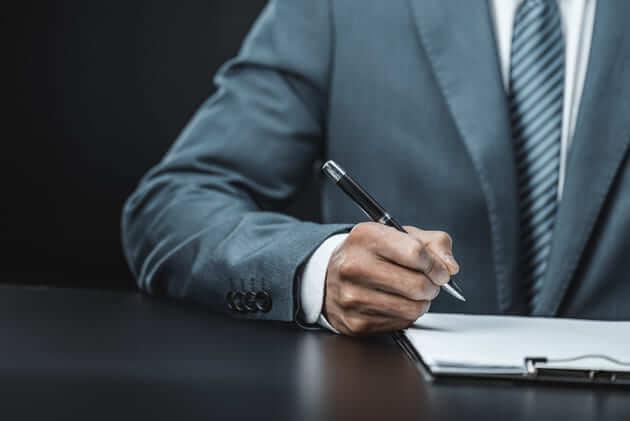 Мужчина в пиджаке заполняет документ ручкой
