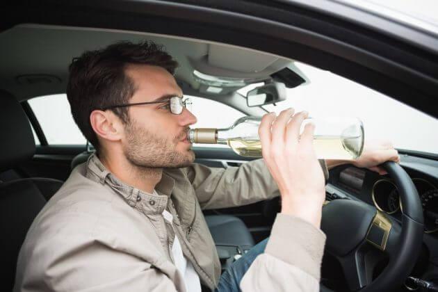Водитель пьёт за рулем авто алкоголь
