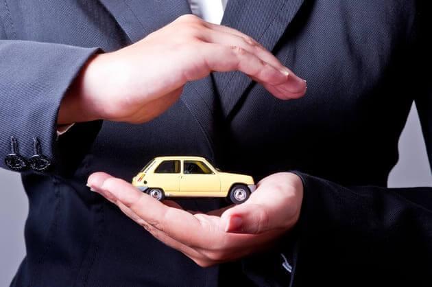 двумя руками закрывается игрушечное авто — метафора защиты