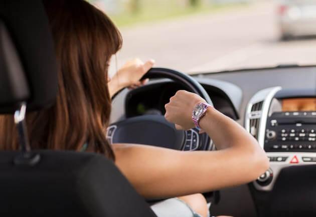 Женщина водитель смотрит на часы