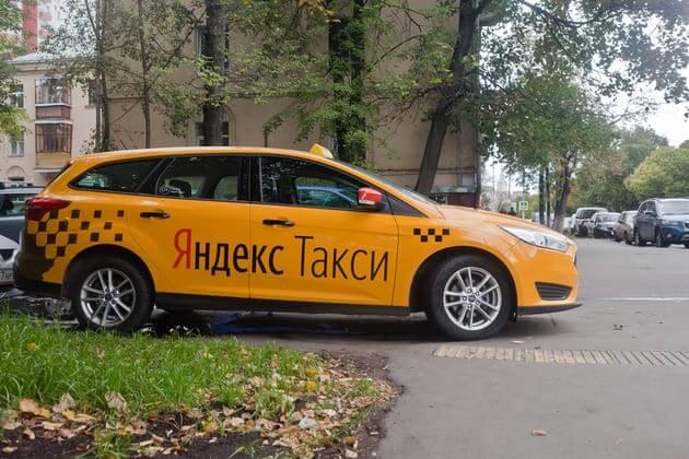 Авто от яндекс такси припаркованное на газоне