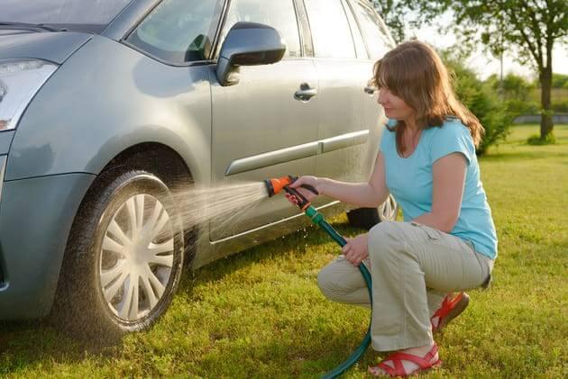 Женщина моет авто на газоне