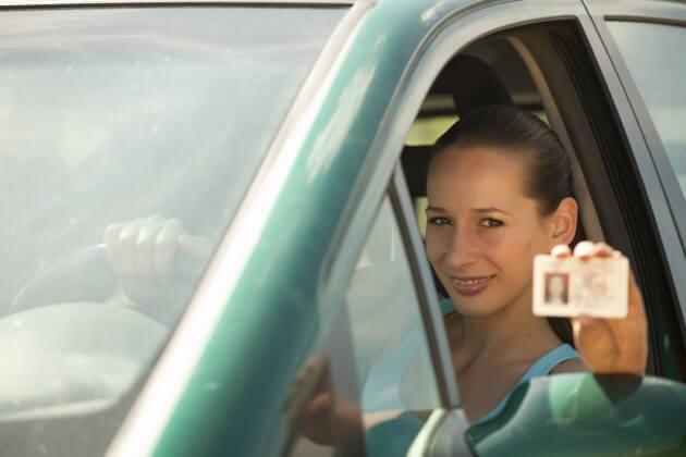 женщина держит водительские права