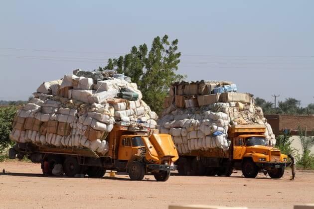 Перегруженные два грузовика в бедной стране